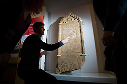 © Licensed to London News Pictures 25/01/2016, Cirencester, UK. Collections officer James Harris (2L) looks at a unique Roman tombstone, found in February 2015, here on display for the first time at Corinium Museum in Cirencester. The tombstone was found near skeletal remains thought to belong to the person named on its inscription, making the discovery unique. After being found during excavation works on a former site of a garage, archaeologists said they believed it marked the grave of a 27-year-old woman called Bodica. Other theories point to it possibly belonging to a couple - as skeletal remains of women were found nearby.<br />