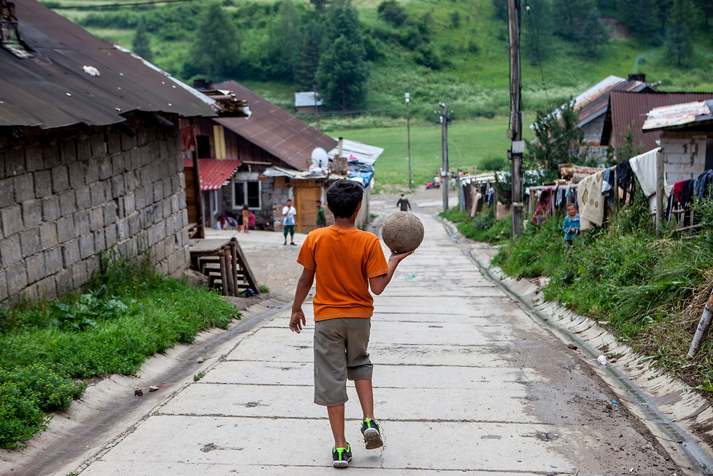 "A teenager is heading to the footbal field with a ball in his hands at the Roma part of the district ""Podsadek"" in eastern Slovakia. The city of Stara Lubovna is located about 100 km from Kosice in northeast Slovakia. The town has a population of 16350, of whom 2 060 (13%) are of Roma origin. The majority of Roma live in the Podsadek district, where 980 (74%) out of 1330 inhabitants are Roma."