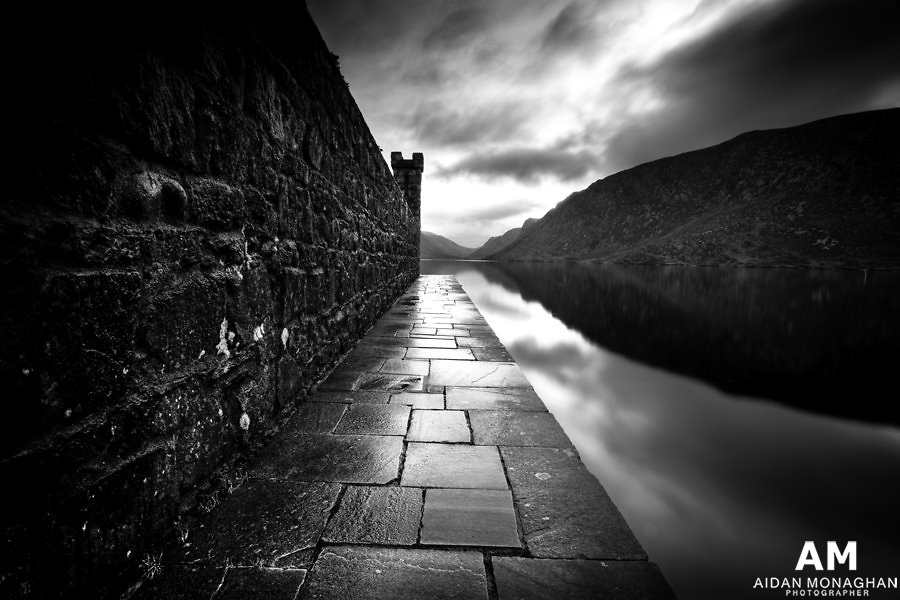 Glenveagh castle, County Donegal<br /> Glenveagh castle lies in the heart of the Derryveagh Mountains Co. Donegal. It is a remote and hauntingly beautiful wilderness of rugged mountains and pristine Loughs. The Castle steps down to series of majestic Loughs. Here the boat house seems to join seamlessly with the deep dark peatland Lough of Barra bog, Meenachullion and Crockastoller with their backdrop of mountains, glens and woods. The photograph was taken just after sunset. I converted the image to black and white as I wanted to emphasize the textures within the scene. The planar nature of the paving slabs of the boat house contrast against the crisp glass like surface of the still water and the deep inky black reflections of the mountains within this petland Lough environment.<br /> <br /> Northern Ireland Landscape Photography, landscape photography of Northern Ireland, Photography Northern Ireland, Landscape Photography of Ireland and Great Britain, Landscape Photography of Ireland, Ireland landscape photography, buy photos of Ireland, landscape photographer Ireland, photographs and pictures of Ireland, Irish landscape photography, fine artlandscape photos of Ireland, fine art landscapes &amp; seascapes,  Irish photographer, landscape North and South of Ireland, Pictures of Ireland, Irish Pictures, Irish Landscapes, Photographs of Ireland