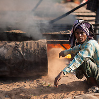 A laborer throws sand onto the fire that heats the tar that workers manually pour tomlay the new road in Srimongol in the tea growing region of north east Bangladesh