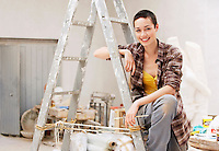 Female interior decorator sitting on ladder in work site portrait