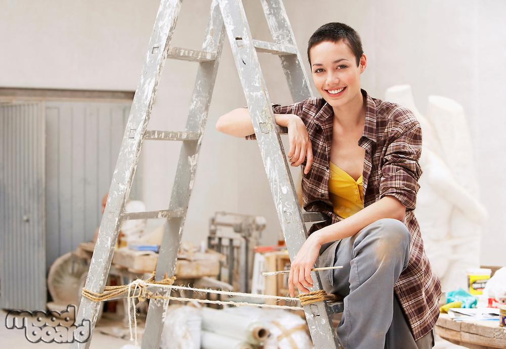 Female interior decorator sitting on ladder in work site portrait
