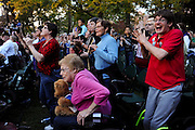 Noah Hogan, (far right in red) 24, of Athens, Ohio leaps out of his wheel chair and Doletta Smith (center in pink), age 81 of Parkersburg, W. Va. struggles to get to her feet as President Barack Obama takes the stage to give a speech at Ohio University on October 17, 2012 in Athens, Ohio.