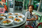 """11 JANUARY 2013 - BANGKOK, THAILAND:    A Muslim woman packages community lunches to be eaten after noon prayers at a Mosque in the Ban Krua neighborhood in Bangkok. The Ban Krua neighborhood of Bangkok is the oldest Muslim community in Bangkok. Ban Krua was originally settled by Cham Muslims from Cambodia and Vietnam who fought on the side of the Thai King Rama I. They were given a royal grant of land east of what was then the Thai capitol at the end of the 18th century in return for their military service. The Cham Muslims were originally weavers and what is known as """"Thai Silk"""" was developed by the people in Ban Krua. Several families in the neighborhood still weave in their homes.                 PHOTO BY JACK KURTZ"""
