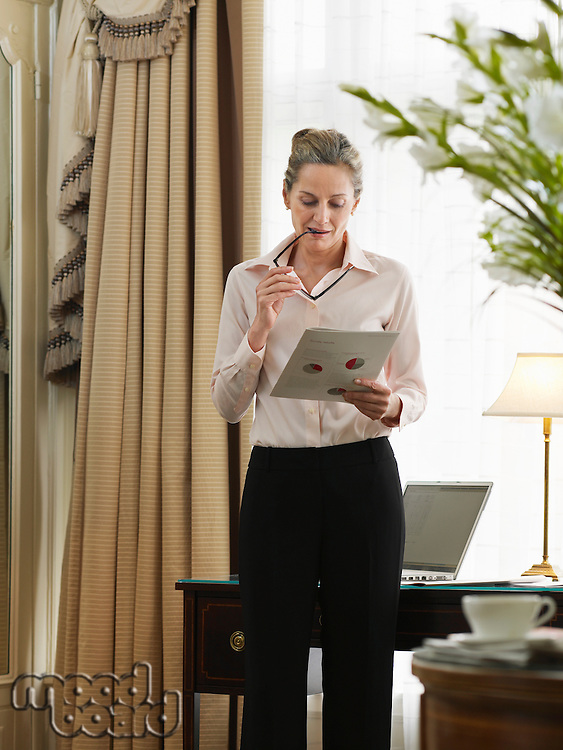 Business woman reading document in home office