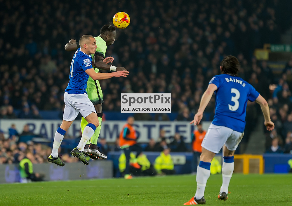 Manchester City defender Bacary Sagna  climbs over Everton midfielder Leon Osman to win a header in the Football League cup semi-final first leg at Goodison Park, Liverpool