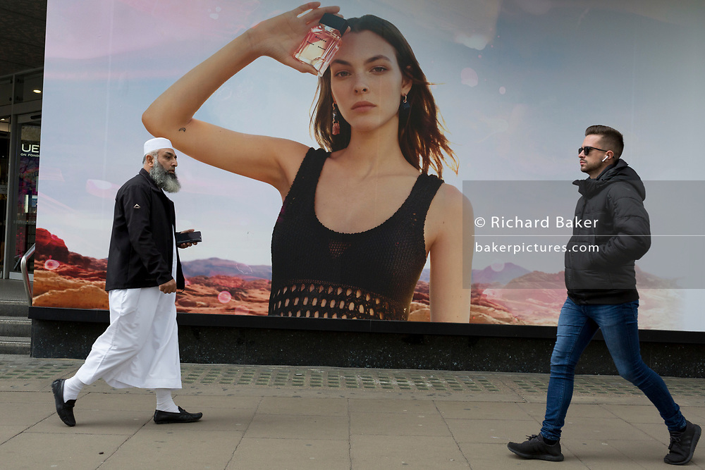 An elderly Islamic gentleman and a young man walk past a billboard ad featuring the face of a model advertising a perfume outside the retailer Debenhams on Oxford Street, on 16th April 2018, in London, England.