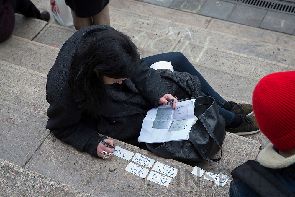 Anne Manteleers draw the faces of the victims of Maelbeek Metro station explosions, which she hand out to whoever are interested, to make them still be. Here at the stairs to the old Stock Exchange building at Brussels Place de la Bourse. Here people of all nationalities and faith show solidarity grief in the morning Thursday 24 March 2016. Photo: Erik Luntang