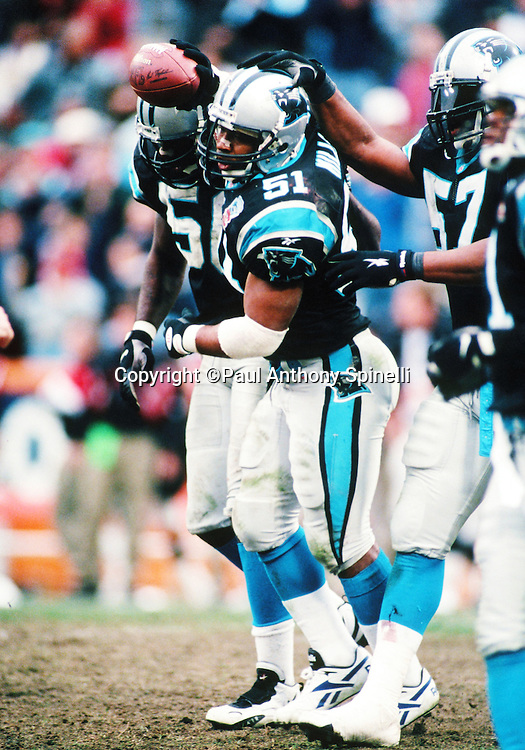 Carolina Panthers linebacker Sam Mills (51) gets a pat on the head from a teammate as he waves the ball in the air in celebration during the NFL football game against the Atlanta Falcons on Dec. 17, 1995 in Charlotte, N.C. The Panthers won the game 21-17. (©Paul Anthony Spinelli)