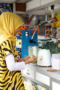 Nur Khayati, 24, making a  fruit smoothie.<br /> <br /> Nur was working in a restaurant when she downloaded the Usaha Wanita app. She wasn't planning to go into business then but the stories and advice about the need for women to be independent inspired her so much that she decided to invest her savings in setting up a juice stall.<br /> <br /> Her fruit is purchased daily and the juices are freshly prepared in front of the customer. <br /> <br /> Her business is just four months old but is already thriving. She has been able to give her parents 6 million rupiah, which they are investing in land to increase the size of their fruit farm. <br /> <br /> She is also opening a new booth in another part of town in two weeks time.