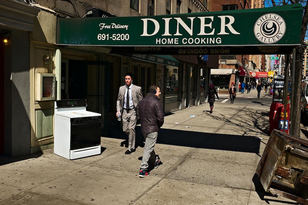 Stove on sidewalk below diner sign, New York, NY, US
