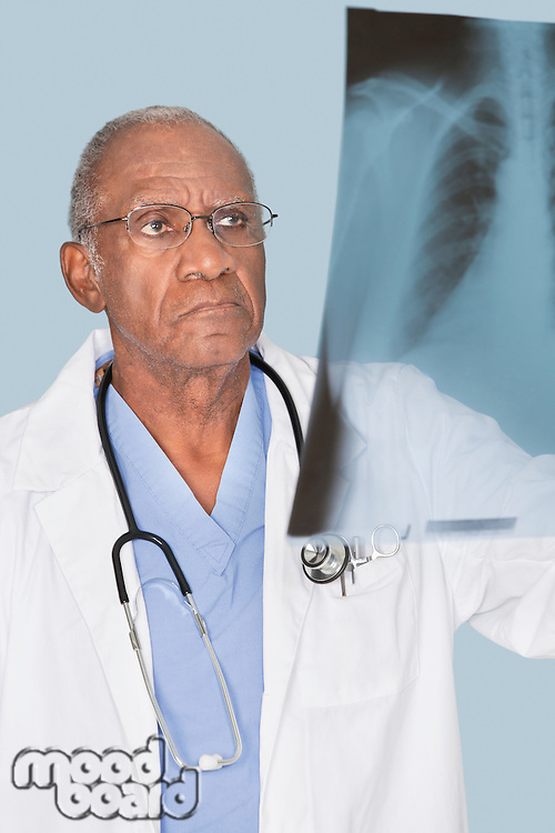 African American senor doctor analyzing x-ray report over light blue background
