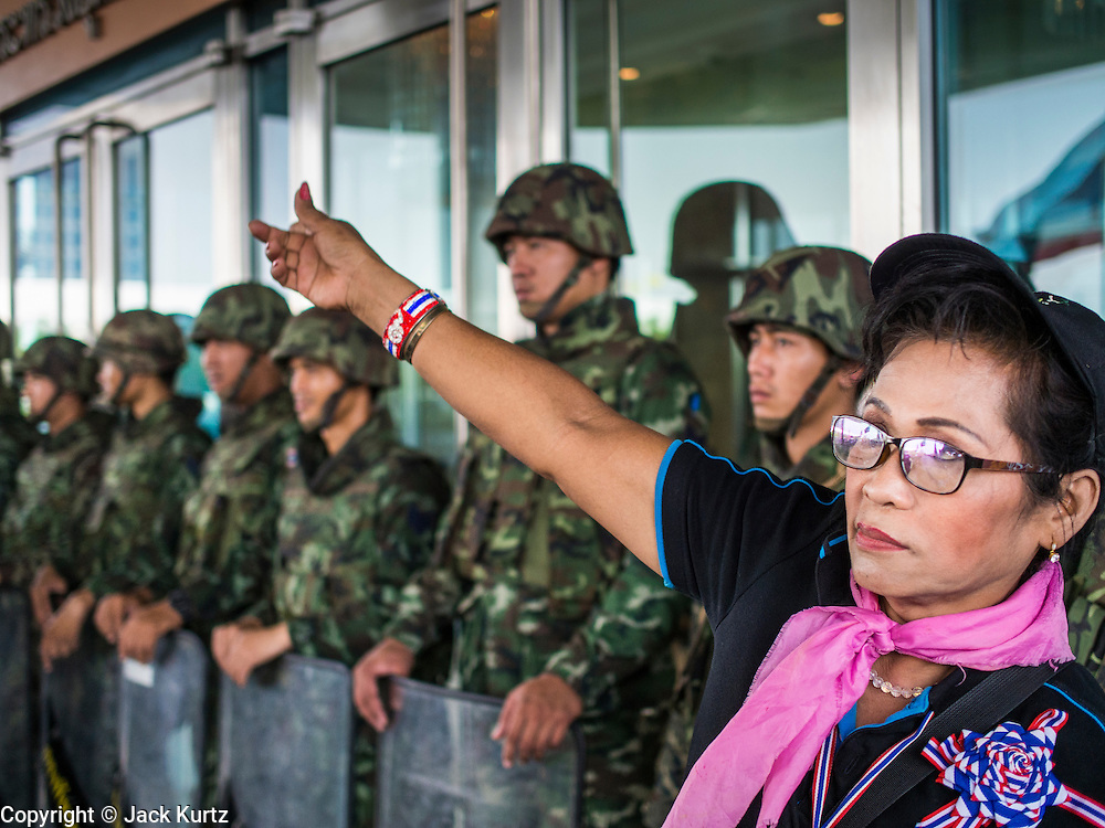 "08 APRIL 2014 - BANGKOK, THAILAND:  An anti-government protestor blocks the entrance to the Thai Ministry of Justice, which was guarded by Thai soldiers. Several hundred anti-government protestors led by Suthep Thaugsuban went to the Ministry of Justice in Bangkok Tuesday. Suthep and the protestors met with representatives of the Ministry of Justice and expressed their belief that Thai politics need to be reformed and that corruption needed to be ""seriously tackled."" The protestors returned to their main protest site in Lumpini Park in central Bangkok after the meeting.   PHOTO BY JACK KURTZ"