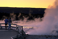 Tourists watching Fountain Geyser at sunset, Fountain Paint Pot area, Yellowstone National Park, MONTANA