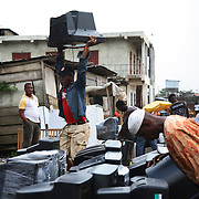 Electronic waste export to Nigeria...Alaba International Market, one of the largest markets for electronic goods in West Africa.  New and old - and a lot of non-working electronic goods such as TVs and computers come in to the market via Lagos harbour from the US, Western Europe and China...Container 4629416 from the UK is being emptied for its load, including the TV tracked by Greenpeace...The shipment - TV-set originally delivered to municipality-run collecting point in UK for discarded electronic products - was tracked and monitored by Greenpeace using a combination of GPS (Global Positioning System using satellites), GSM (positioning using data from mobile networks to triangulate approximate positions) and an onboard radiofrequency transmitter (used for making triangulations in combination with handheld directional receivers used by team on ground) is placed inside the TV-set.  The TV arrived in Lagos in container no 4629416.