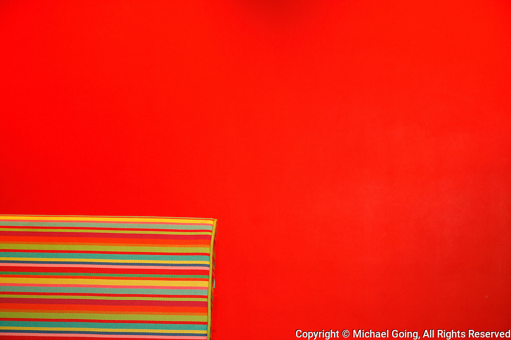 Library room of MOCA Los Angeles with portion of red, green, yellow striped couch against red wall