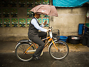 16 JULY 2013 - BANGKOK, THAILAND:   A person rides their bike in the rain in Bangkok.     PHOTO BY JACK KURTZ