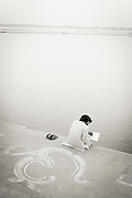 A man sitting by the Ganges River an early morning, Varanasi (Benares), India