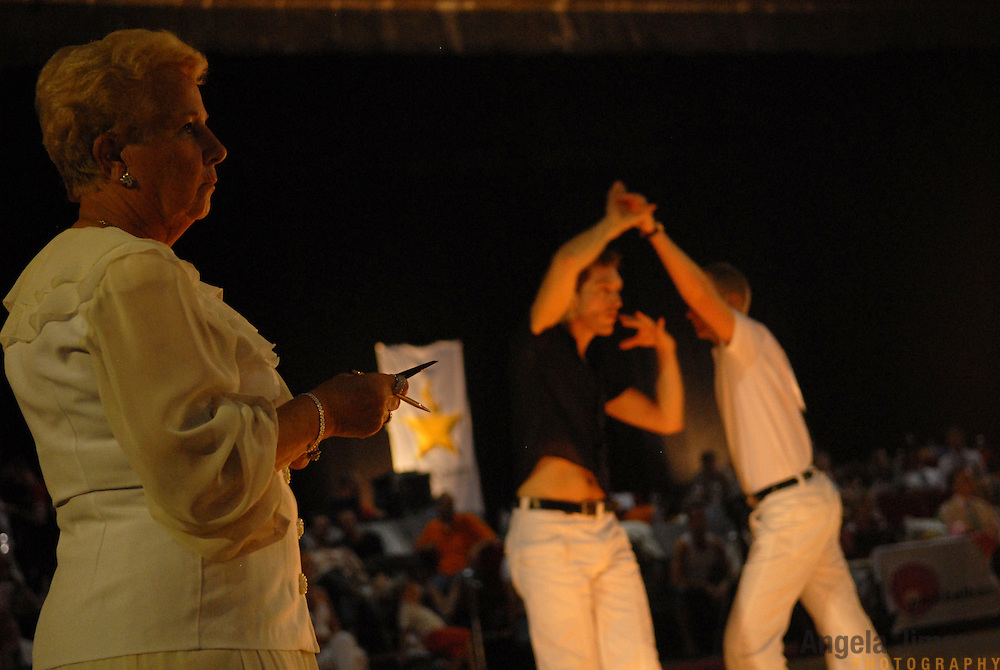 """Conny Degraaf, left, a professional judge of amateur and latin ballroom (and a 9-time former Belgian ballroom dancing champion)from Antwerp, Belgium, judges the adult men's latin division of the same-sex ballroom dancing competition during the 2007 Eurogames at the Waagnatie hangar in Antwerp, Belgium on July 14, 2007. ..""""I like it,"""" said Degraaf, who had never before judged or even seen a same-sex dancing event. """"I was a little afraid. I've been judging 20 years...but it was just like normal dancing.  I like it.""""..Over 3,000 LGBT athletes competed in 11 sports, including same-sex dance, during the 11th annual European gay sporting event. Same-sex ballroom is a growing sports that has been happening in Europe for over two decades."""