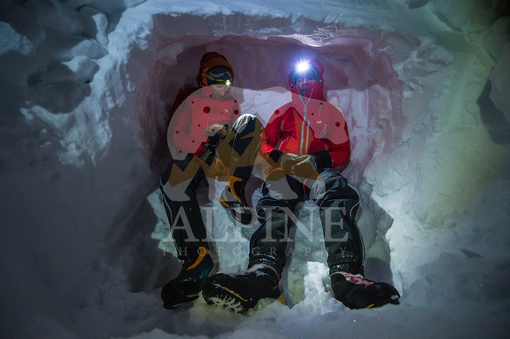 Two male mountaineers rest in an improvised snow cave on a cold winter night on Glacier Blanche.