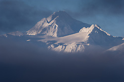 Four Winds Mountain near Haines, Alaska and near the border with Alaska and British Columbia, Canada rises out of low-lying clouds. This view of the mountain is from the Alaska Chilkat Bald Eagle Preserve. Mountains in the Haines area are a popular destination for heli-skiing.