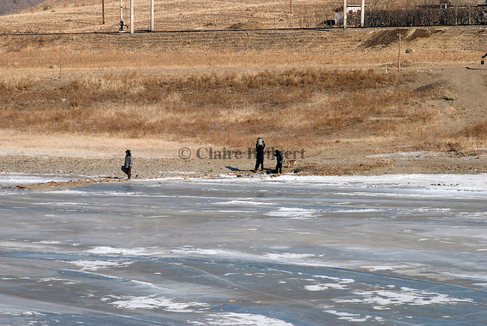 North Korean digging in the frozen Tumen river to get some water near Hoeryong. Water pipes often freeze during winter and most countryside villages have no running water. Soldiers watching the border have the right to shoot whoever tries to cross the river to escape to China.