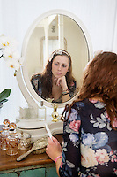 Pensive woman sitting at dressing table