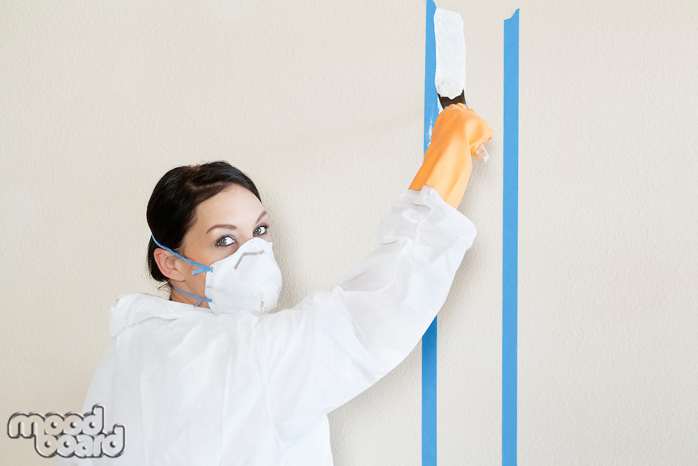 Portrait of a female worker in protective workwear painting wall