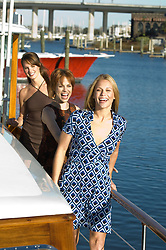 Three women walking on a boat in a Marina, Charleston, SC