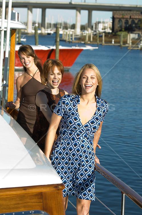 Three women walking on a boat in a Marina, Charleston, SC