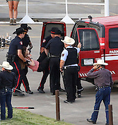 Police carry out one of the two protesters who was chained to the infield fence during day one of the Rangeland Derby at Stampede Park in Calgary on Friday July 4, 2014. (Jenn Pierce/Calgary Herald)