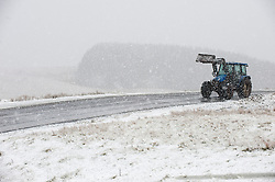 © Licensed to London News Pictures. 21/03/2017. Mynydd Epynt, Powys, Wales, UK. On the Spring Equinox, a tractor drives along a minor road in snow and strong winds which arrived this afternoon on the high moorland of the Mynydd Epynt range between Garth and Brecon in Powys, Wales, UK. Photo credit: Graham M. Lawrence/LNP