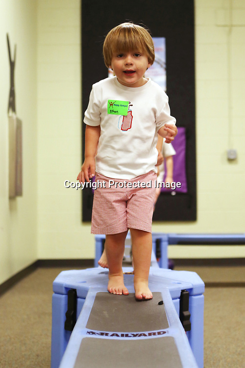 "Ethan Decker, 2, walks along the balance beam as he plays in the Zoom Room Monday morning during the ""We Love Our Moms!"" Hip Hoppers session at Healthworks!."