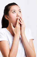 Shocked young woman with hands over mouth against white background