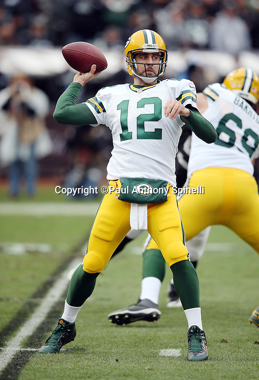 Green Bay Packers quarterback Aaron Rodgers (12) throws a first quarter pass during the 2015 week 15 regular season NFL football game against the Oakland Raiders on Sunday, Dec. 20, 2015 in Oakland, Calif. The Packers won the game 30-20. (©Paul Anthony Spinelli)