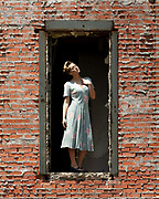 Model Brenna Smith poses in an elevated cargo door in vintage 1940s dress and hair at the abandoned Imparial Sugar mill, Sugar Land, Texas. By Gerard Harrison fashion photographer.