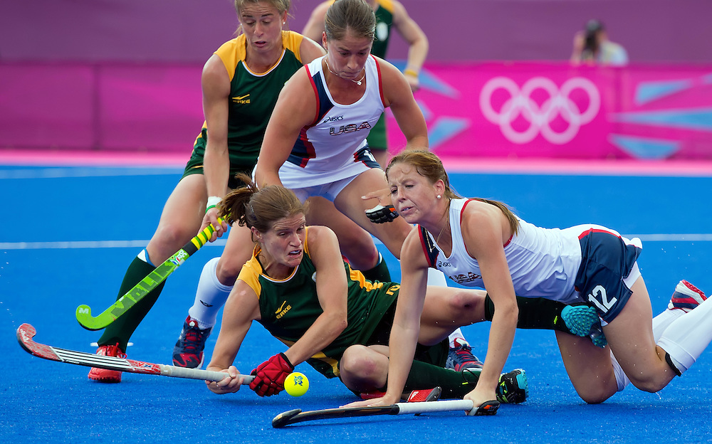 South Africa's Jennifer Wilson, lower left, tangled with Julia Reinprecht, lower right, during second half action in the women's hockey preliminary pool play at Riverbank Arena during the 2012 Summer Olympic Games in London, England, Monday, August 6, 2012. South Africa won the match 7-0. (David Eulitt/Kansas City Star/MCT)