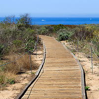 Photo of wooden walkway leading to the Pacific Ocean at Crystal Cove State Park in Laguna Beach in Orange County Southern California.