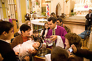 Father Xavier Osvaldo, saying mass at St. Ann's Catholic Church in Shoreditch. The congregation for 12 noon mass on sunday is almost exclusively Brazilian. Father Osvaldo performing a baptism.