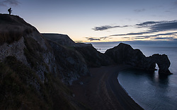 © Licensed to London News Pictures. 05/11/2016. Lulworth, UK.  A photographer waits at first light for sunrise at Durdle Door on the Jurassic Coast in Dorset this morning, 5th November 2016.  Photo credit: Rob Arnold/LNP