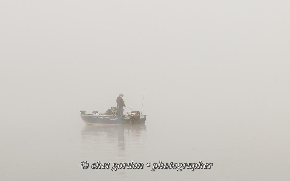 A fisherman works in the fog on Greenwood Lake, NY on Friday morning, November 27, 2015.  © Chet Gordon • Photographer