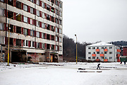 A child is playing at the Lunik IX housing estate which is home of the largest Roma community in Slovakia. On the left side a decript building, on the right a new housing complex standing on a place where one of the older buildings was demolished. The community is located a few kilometers away from the historical city centre, on the outskirts of the eastern Slovakian city of Kosice. Since the beginning of the 1980s a large number of the Roma residents living in the city and in nearby settlements have been moved to Lunik IX. Lunik IX has officially 6542 registered (12/2015) inhabitants and almost all of them are of Roma ethnicity.