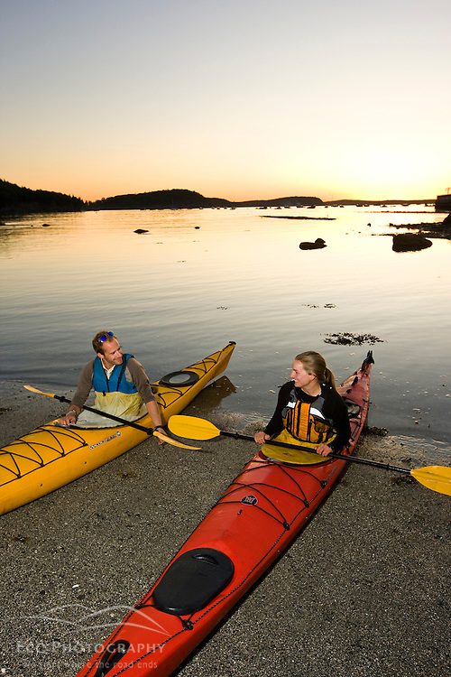 Two kayakers on the Bar Island bar prepare to paddle at dawn in Bar Harbor, Maine.