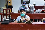 A cigarmaker called a torcedor stacks completed cigars at her rolling table at the Santa Clara cigar factory in San Andres Tuxtlas, Veracruz, Mexico. The factory follows traditional hand rolling using the same process since 1967 and is considered by aficionados as some of the finest cigars in the world.