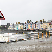 A windy and wet storm lashes the brightly colored houses on the waterfront in Aberystwyth on the western coast of Wales. Sea water laps over the sea wall, flooding the parking lot in the foreground.