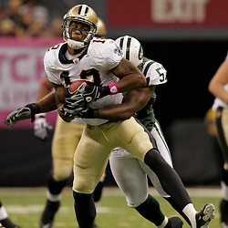 2009 October 04: New Orleans Saints wide receiver Marques Colston (12) is hit by New York Jets linebacker Bart Scott (57) during the first half of a week four regular season game between the New Orleans Saints and the New York Jets at the Louisiana Superdome in New Orleans, Louisiana.