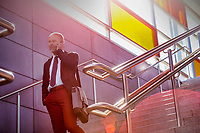 Portrait of mature businessman talking on smartphone while standing on stairs