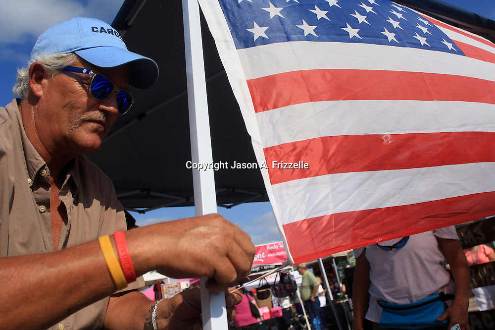 Joel Brown ties an American Flag to Sweet Bessie's Southern Mixes booth at Leland's Founder's Day festival.