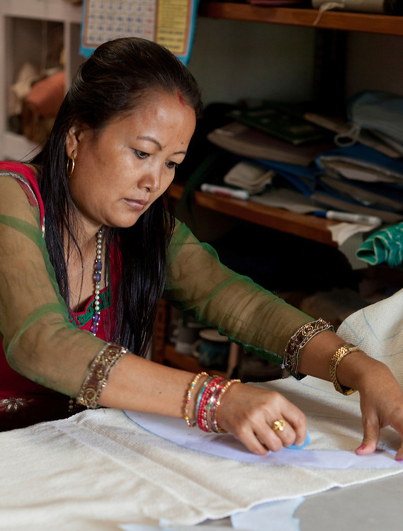 A Nepali woman laying out patterns for clothing at Womens Skills Development Project in Pokhara, Nepal. The WSDP was set up in 1975 as a non-profit, fair trade organization to help disadvantaged women in Nepal.