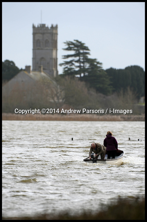 A couple use their boat to get around the roads cut off on the Somerset Levels which are Flooded due to heavy rain in January. London, United Kingdom. Tuesday, 4th February 2014. Picture by Andrew Parsons / i-Images